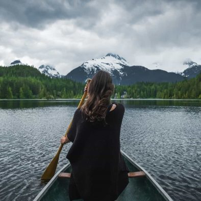 a girl rowing a boat in a lake in the mountains