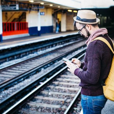 a man on his phone at a train station