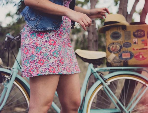 a girl in a flowery dress next to a bike