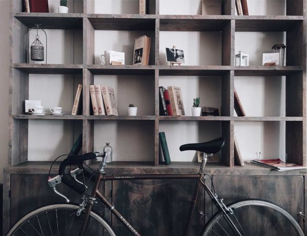 a bookcase with a bicycle leaned against it