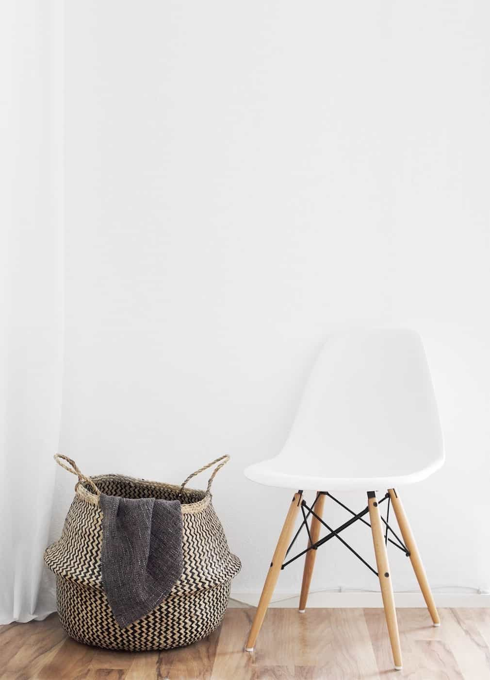 a white chair with wooden legs next to a wicker basket against a stark white wall