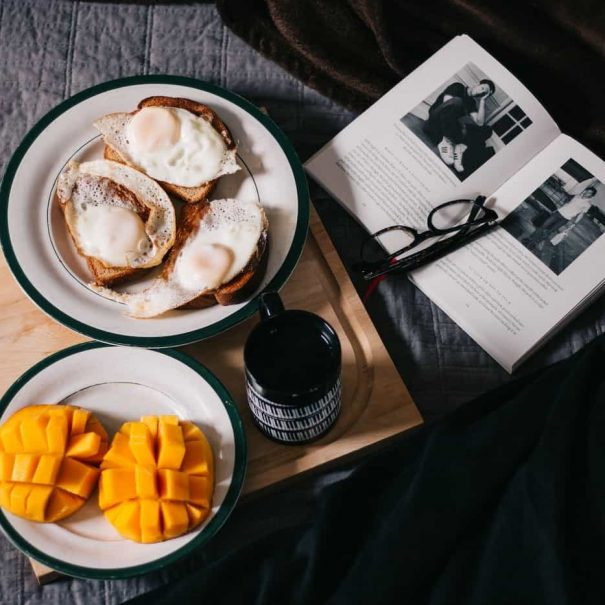 a full breakfast tray next to an open book