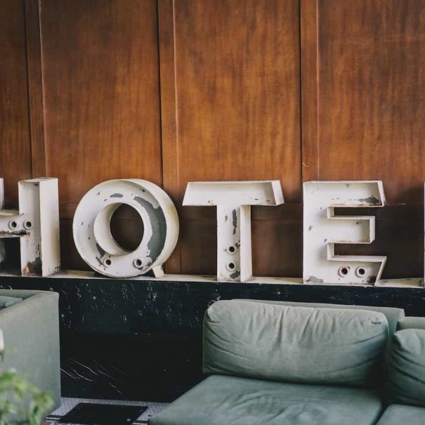 """a white metal sign that reads """"hotel"""""""