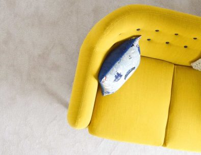 a yellow couch with a nautical pillow on it