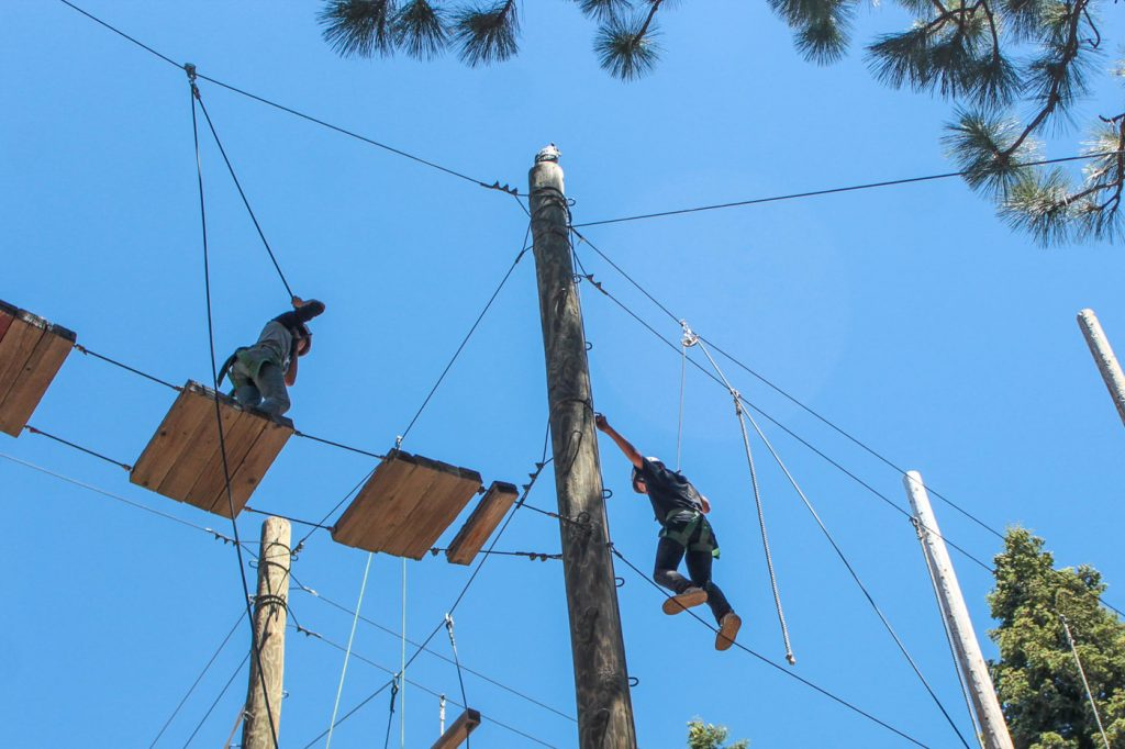 two people traversing a ropes course