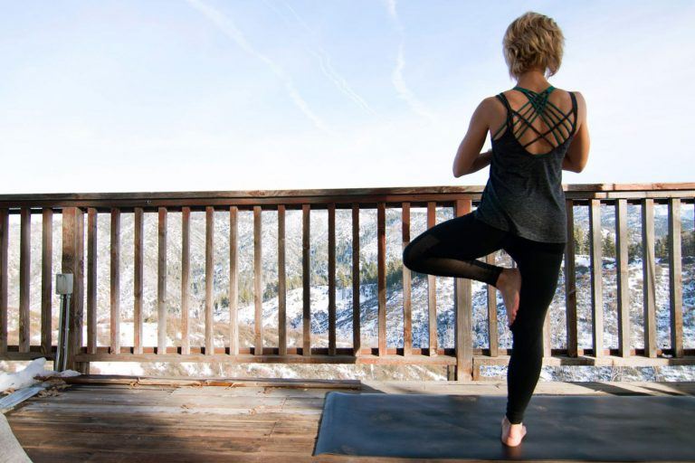 a woman doing yoga on a deck in the mountains