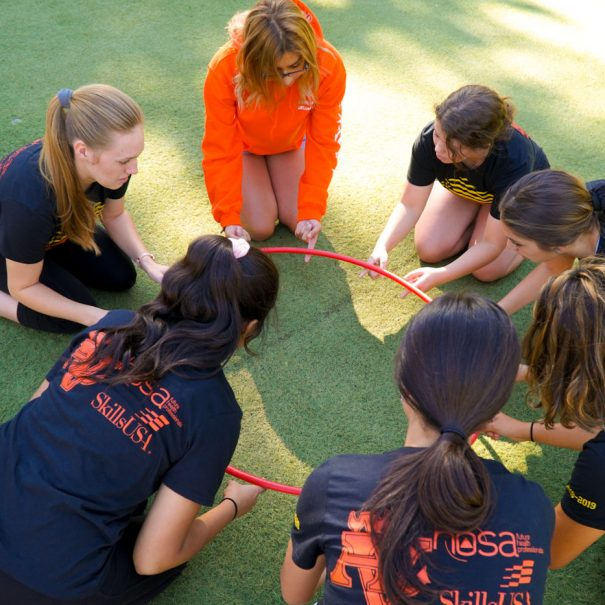 a group of high schoolers in circle formation holding onto a hoola hoop