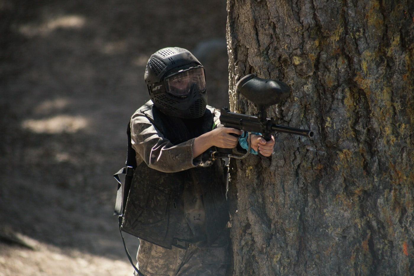 a person taking cover behind a tree while playing paint ball