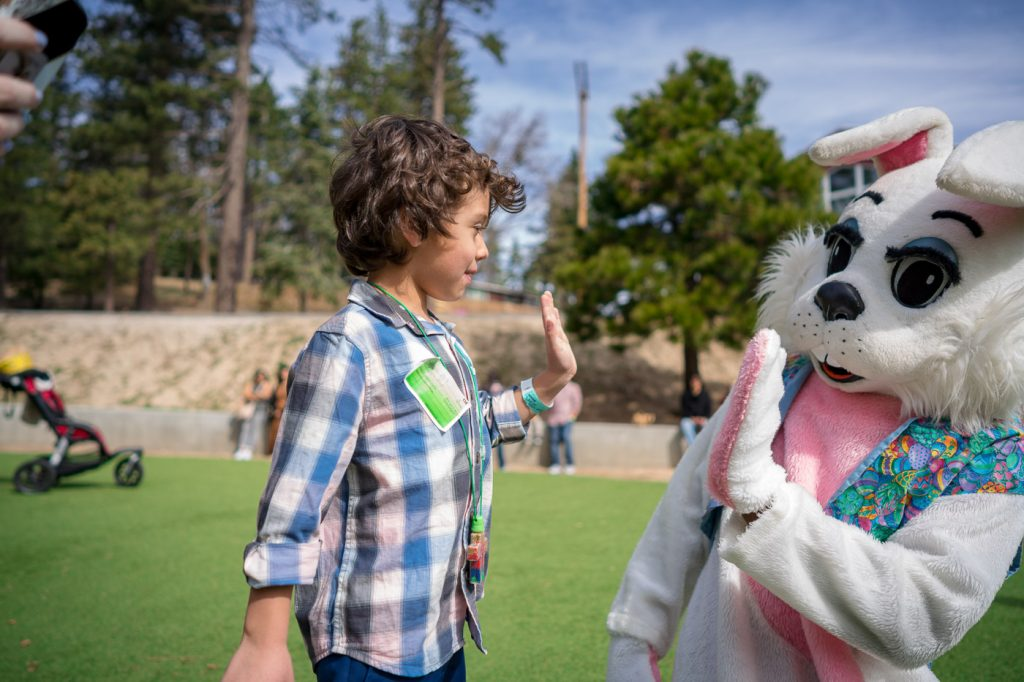 a boy high fiving someone in a bunny costume