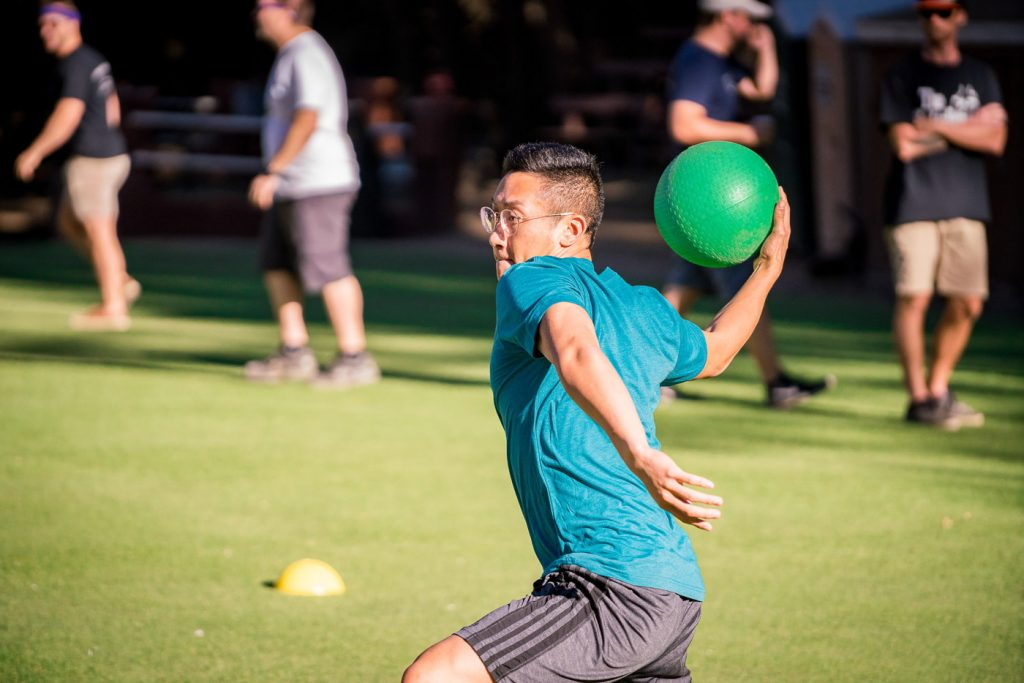 a boy in glasses throwing a green dodgeball